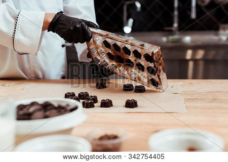 Cropped View Of Chocolatier Holding Chocolate Molds Near Baking Paper And Chocolate Candies