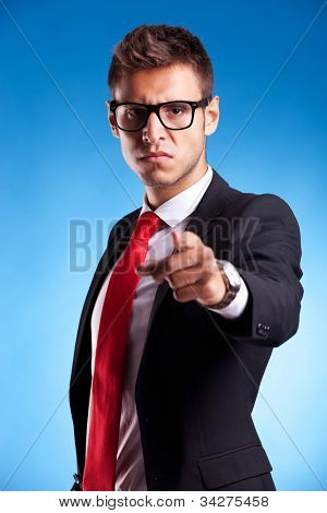 accusing young business man , pointing to the camera on blue background