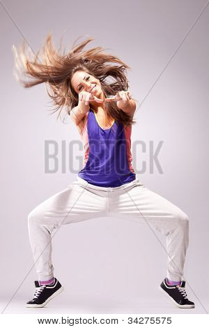 young stylish girl dancing modern ballet dance , with a headbanging move and pointing to you