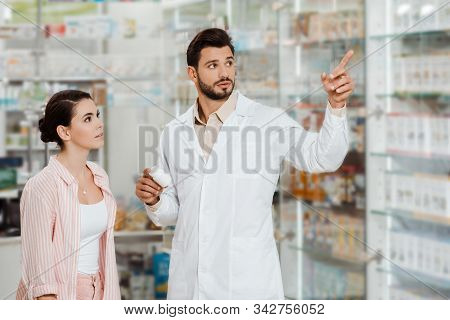 Druggist With Jar Of Pills Pointing At Pharmacy Showcase To Customer