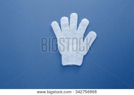 Woman Exfoliating Massage Glove For Shower On Blue Background.