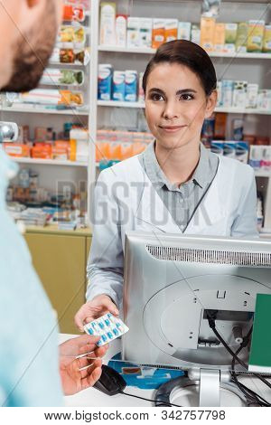 Selective Focus Of Smiling Druggist Giving Pills To Customer At Pharmacy Counter