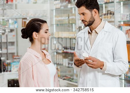 Side View Of Druggist Showing To Customer Jar Of Pills By Pharmacy Showcase