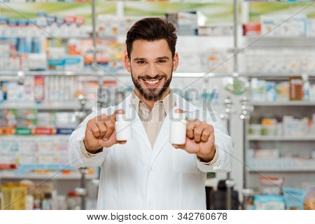 Smiling Druggist Looking At Camera And Holding Jars With Pills