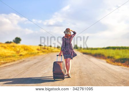 Amazing Woman In Summer Dress And Hat Hitchhiking With Suitcase. Female Walking On The Road With Lug