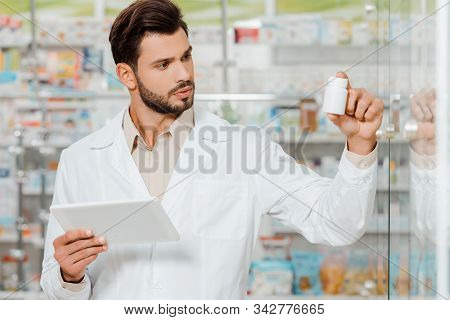 Handsome Druggist Holding Digital Tablet And Looking At Jar Of Pills