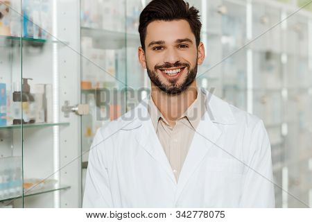Handsome Druggist Smiling At Camera By Pharmacy Showcase