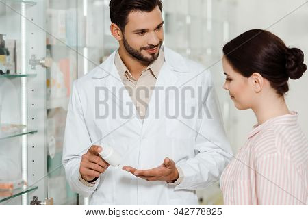 Smiling Druggist Showing Jar With Medicament To Customer By Pharmacy Showcase