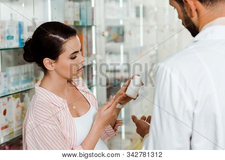 Selective Focus Of Pregnant Woman Holding Jar With Pills By Druggist In Pharmacy