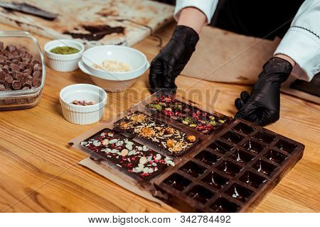 Cropped View Of Chocolatier In Black Latex Gloves Holding Chocolate Molds With Prepared Chocolate Ba