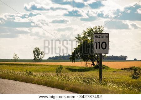 110 Km Maximum Speed Limit Sign On The Roadside Against Yellow Prairies And Plains View On The Canad