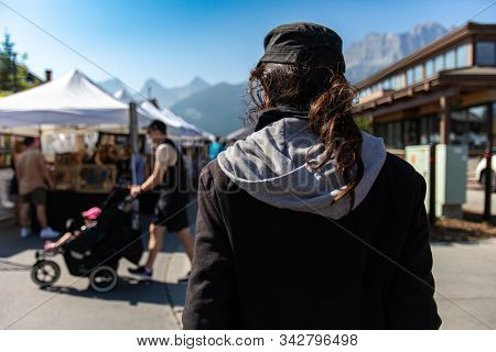A Man With Dark Unkempt Hair In A Ponytail Is Seen From The Back At The Entrance To A Local Fair For