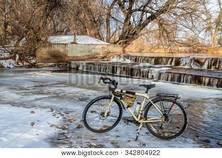 touring bike and a river in fall scenery - Poudre River below a diversion dam in Fort Collins northern Colorado, commuting concept
