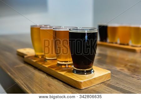 Flight Of Craft Four Of Different Beers Glasses With Black Beer On A Wooden Tray. During A Tasting S