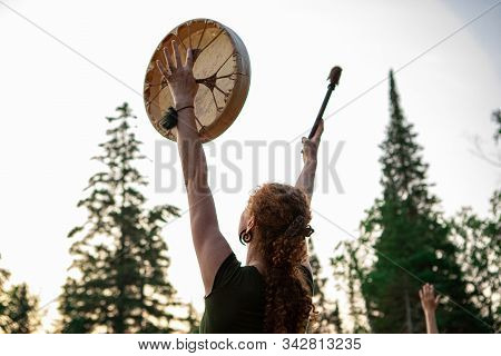 A Spiritual Redhead Women Is Viewed From Behind As She Raises A Native Drum And Drumstick With Trees