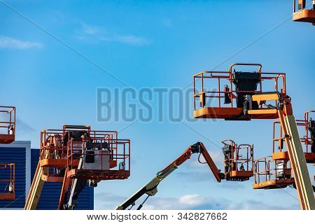 A Group Of Raised Cherry Pickers, Aerial Work Platforms, Are Seen In An Elevated State In Storage, H