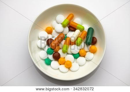 Plate with set of pills, tablets, vitamins, drugs, gel capsules, medicament and food supplement for health care. Pharmaceutical industry. Pharmacy.