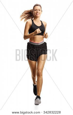 Full length portrait of a young woman in shorts running isolated on white background