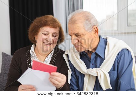 Senior Couple Standing On The Couch And Reading A Letter Received. Portrait Of A Happy Senior Couple