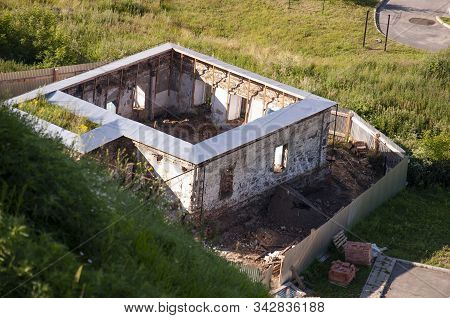 Old Destroyed Stone House On The Yard With Trees Around. Poverty And Misery, Summer