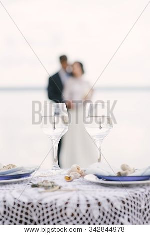 Two Glasses On The Background Of A Loving Couple Of The Bride And Groom Blurr