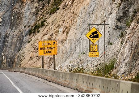 Steep hill 6 percent ahead for 2.6 km, truck gear down. 500 m runaway lane. Warning road signs and cement barriers on the right roadside poster