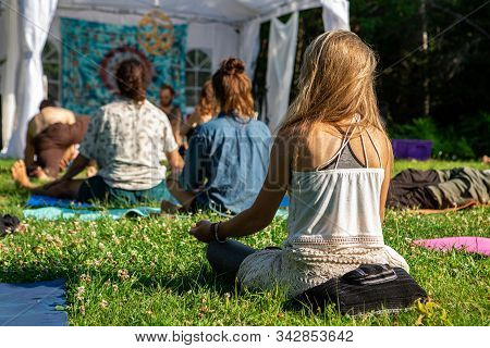 Back View Of Blonde Girl With A Diverse Group Of People Enjoying Outdoor Meditation Session During A