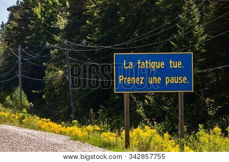 Blue Information Road Sign With French Yellow Writing, Tiredness Kills. Take A Break., On Rural Coun