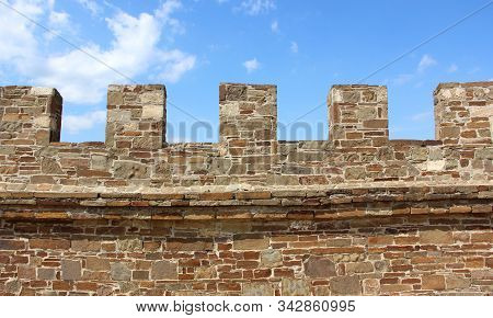 Wall With Battlements, The Exterior Of An Ancient Fortress. Stone Background, Texture. Architecture.