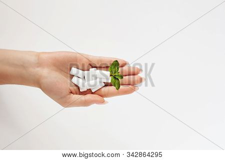 Chewing Gum With A Mint Leaf  In  A Female Hand On A White Background. Fresh Breath, Mint Chewing Gu