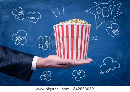 Male Hand Holding Popcorn Bucket On Blue Background