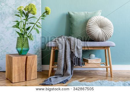 Modern Scandinavian Home Decor Of Living Room With Gray Bench, Wooden Cube, Flowers In Vase, Pillows