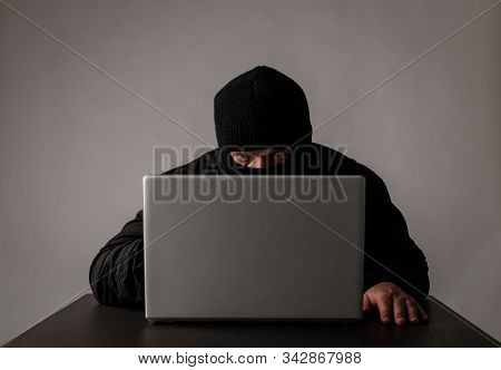 Hacker In Mask Using A Laptop To Browse The Net. Terrorist And Virtual Space. Unsafe Zone Concept.