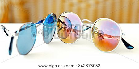 Glasses For Sun Protection With Blue And Yellow Glasses Lie On The Table.