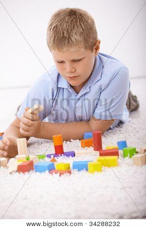 Schüler, die am Boden zu Hause, mit Würfel spielen.
