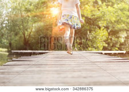 Little girl running in pier at lakeshore with yellow lens flare