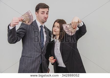 Self-confident Business People Holding Fans Of Money, Looking Pathetic At The Camera.