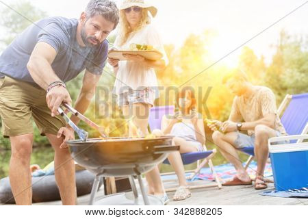 Woman preparing food in barbecue grill with friends on pier