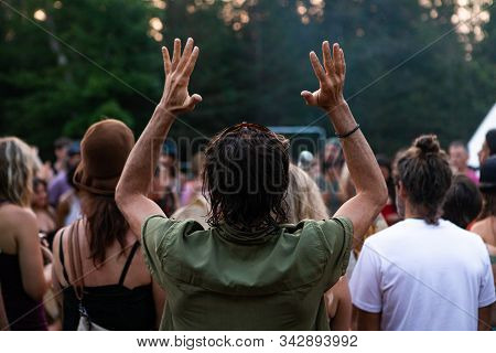 Young Man Wearing Sunglasses On His Head Is Looking At The Sky And Raising His Hands In Awe As He Is
