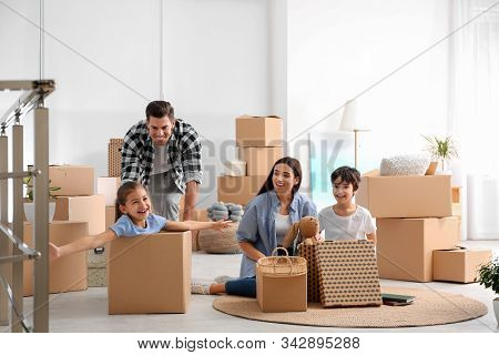 Happy Family Having Fun While Unpacking Moving Boxes At Their New Home