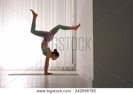 Woman Practicing Downward Facing Tree Asana In Yoga Studio. Adho Mukha Vrksasana Pose