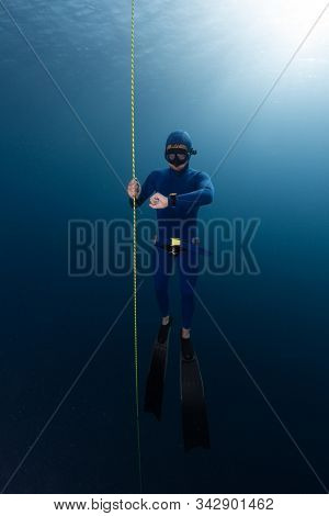 Freediver hangs on the rope in the depth and looks at his watch