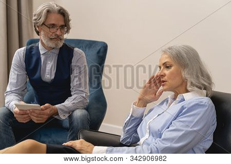 Psychoanalyst Sitting Next To His Female Patient