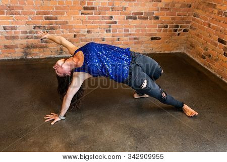 A High Angle Shot Of A Slim Caucasian Woman Transitioning Through Advanced Postures During A Gruelin