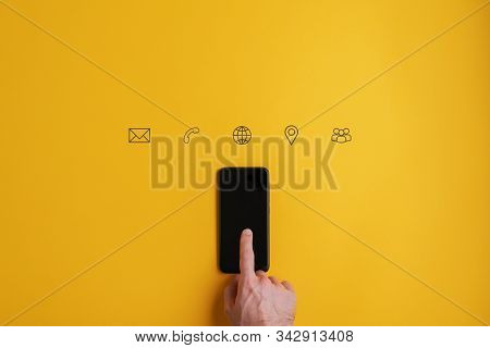 Contact And Communication Icons On Yellow Background Above A Black Smart Phone.