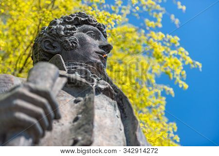 Monument Of Popular Classic Russian Poet Pushkin. Cigaret In Mouth And Tree In Background