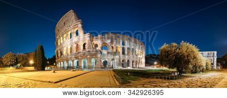 Rome, Italy. Colosseum Also Known As Flavian Amphitheatre In Evening Or Night Time. Panoramic View