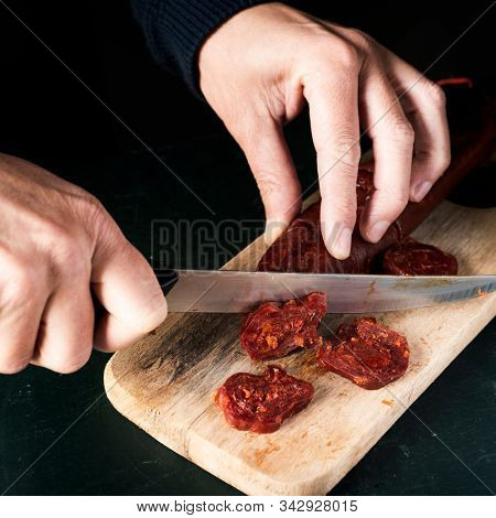 closeup of a man cutting some slices of chorizo, a cured pork sausage typical of spain, with a kitchen knife on a wooden chopping board