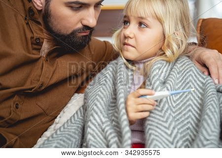 Sick Little Girl Sitting On Couch With Father
