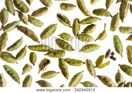 Green cardamom pods scattered on white background.